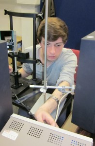 "This photo shows undergraduate student Steven Errington checking the calibration of a mirror stereoscope. This is one of the oldest forms of 3D display, and uses mirrors to present different images to the two eyes. The observer will sit with their head in the headrest in front of Steven, and the two mirrors in front of them will ensure that their left eye views a computer monitor to their left, while their right eye views a different monitor on their right. It's essential the two monitors are aligned both in space and time - that is, that they update their images at exactly the same time. Steven has clamped a photodiode in front of each monitor (that's the white cable running down by his hand) and fed their inputs into an oscilloscope. Photodiodes output a voltage which depends on the light falling onto them, so each new image presented on the computer monitor shows up as a ""blip"" on the oscilloscope. Steven can then check that the blips are occurring at exactly the same time, to sub-millisecond precision."