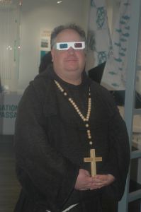 re-enactor dressed as mediaeval monk, wearing anaglypd 3D glasses